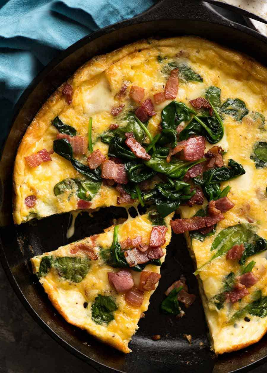 Overhead photo of Frittata with Bacon and Spinach in a black skillet, fresh out of the oven ready to be served