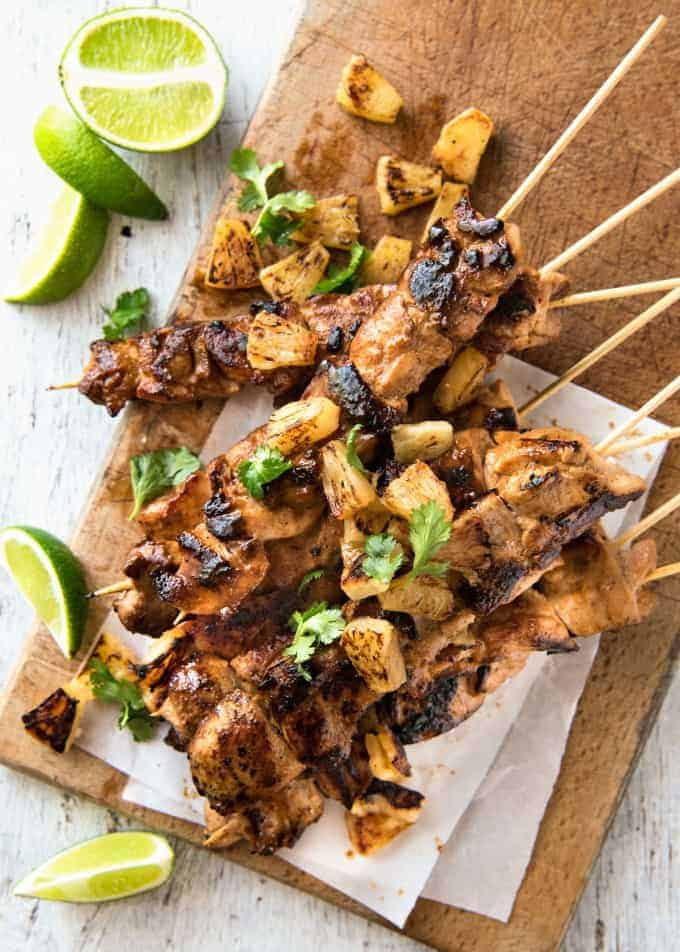 A stack of Pineapple Coconut Hawaiian Chicken Skewers on a wooden board with lime wedges.